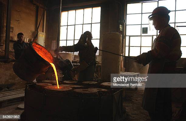 Battaglia artistic foundry in Milan This is the foundry where the works by Italian sculptor Arnaldo Pomodoro are made Some workers pouring melted...