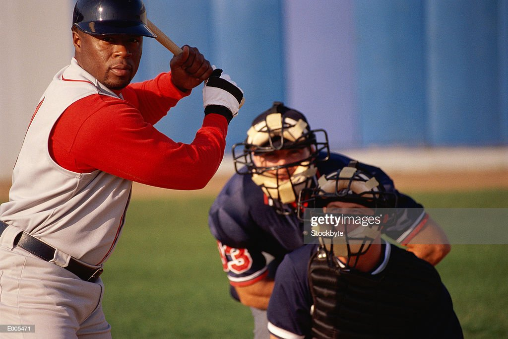 Batter about to hit, umpire and catcher behind : Stock Photo