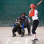 Batter (10-12) at home plate with catcher and umpire in background