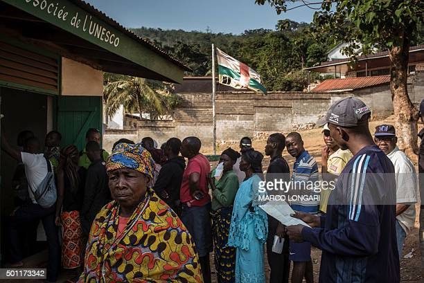 A battered Central African Republic flag flutters as voters queue outside a polling station in Bangui on December 13 2015 to vote for the...