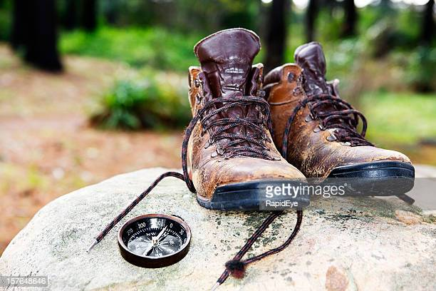 Battered hiking boots and compass rest on rock in clearing