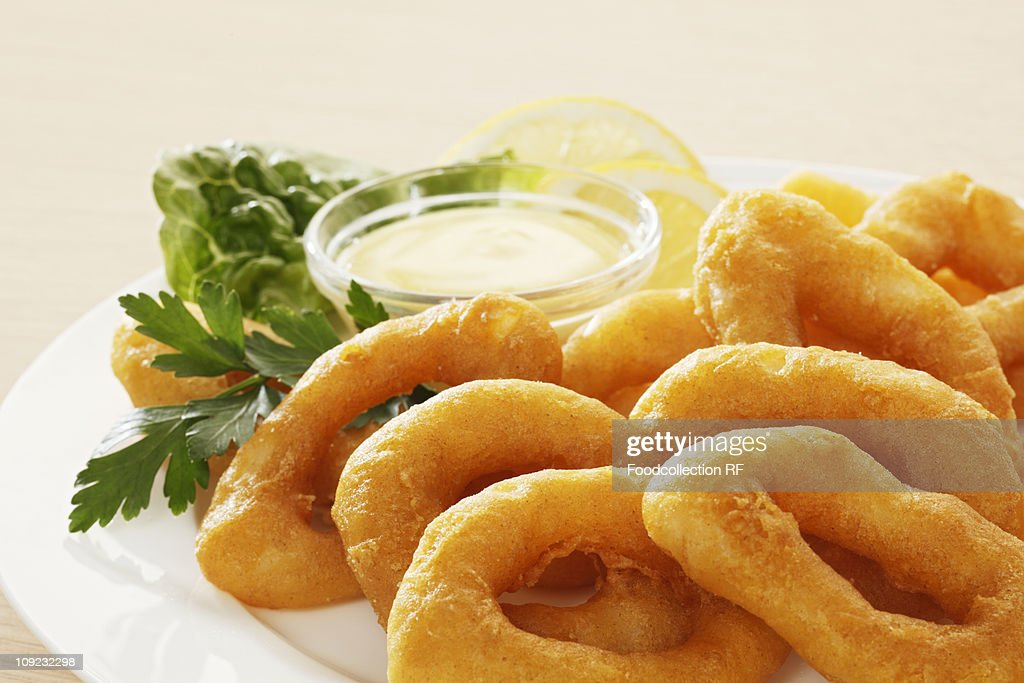 Battered squid rings on plate, close-up : Stock Photo