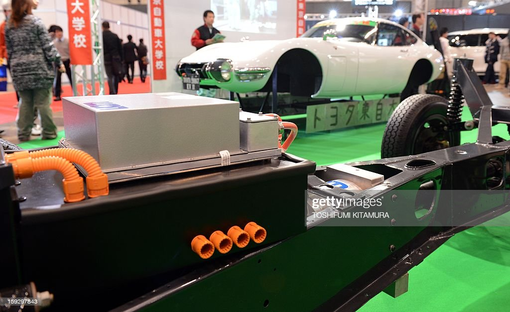 A battery and motor is set up on the original chassis of a 'Toyota 2000GT EV II' electric vehicle, removed from a 1968 Toyota 2000GT (rear) by the Toyota Technical Collage during the Tokyo Auto Salon 2013 exhibition at the Makuhari Messe in Chiba on January 11, 2013. A total of 452 domestic and foreign companies participated in the three-day-long custom car exhibition with some 800 vehicles on display.
