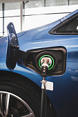 Battery charger in blue electric car at showroom