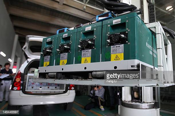 A battery exchange robot changes the batteries to an electric car at China's largest electric vehicle battery recharging station on May 30 2012 in...