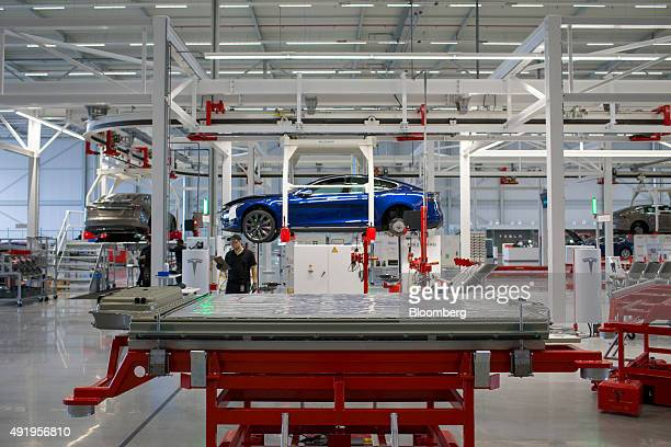 A battery pack stands on a trolley as Tesla Model S automobile sits in a cradle during final assembly at the Tesla Motors Inc factory in Tilburg...