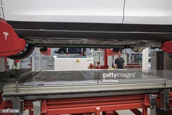 A battery pack stands on a trolley underneath a Tesla Model X sports utility vehicle prior to being fitted during the assembly for the European...