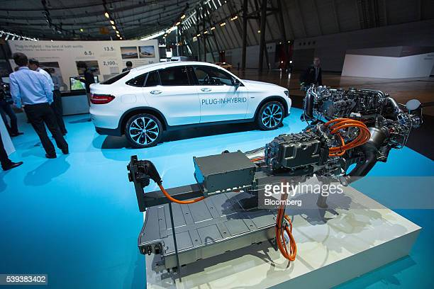A battery sits connected to a new pluginhybrid engine and powertrain system as a MercedesBenz GLC 350e coupe automobile stands beyond during Daimler...