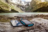 Battery solar energy device on the background of beautiful mountain scenery. Charge smart phone from the solar battery.