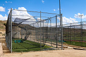 Image of a fully enclosed batting cage.  Batting cages are used to practice hitting the ball in softball and baseball.  The sky overhead is blue with puffy cumulous clouds.  Inside the cage is green,