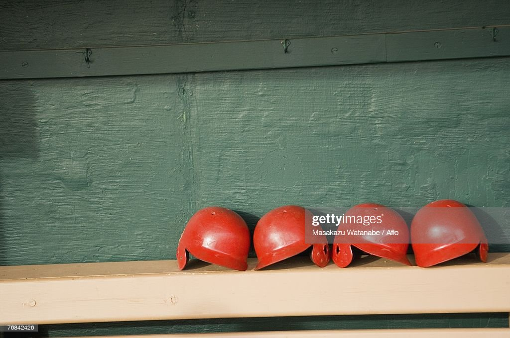 Batting helmets on a bench in a dugout