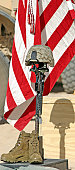 A battlefield memorial cross rifle display stands at attention, during a memorial service.