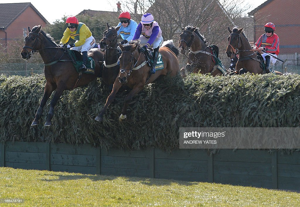 Battlefront ridden by Katie Walsh (L), Rash Move ridden by T Ellis (2nd L) and Sizing America ridden by M Hamill (3rd L) jump Beechers Brook during the Fox Hunters Steeple Chase on the opening day of the Grand National Meeting horse racing event at Aintree Racecourse in Liverpool, north-west England on April 4 2013. The annual three day meeting culminates in the Grand National which is run over a distance of four miles and four furlongs (7,242 metres), and is the biggest betting race in the United Kingdom. AFP PHOTO/ANDREW YATES