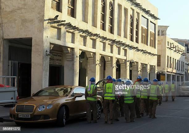 Bauarbeiter auf dem Weg zur Arbeit gehen am Bentley vorbei Souq Waqif