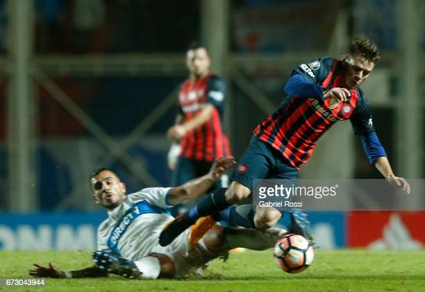 Bautista Merlini of San Lorenzo fights for the ball with Cesar Fuentes of Universidad Catolica during a match between San Lorenzo and Universidad...