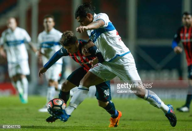 Bautista Merlini of San Lorenzo fights for the ball with Juan Carlos Espinoza of Universidad Catolica during a match between San Lorenzo and...
