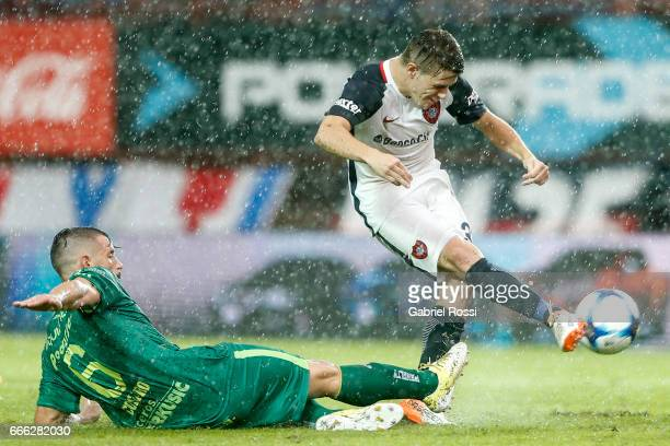 Bautista Merlini of San Lorenzo takes a shot as Guillermo Cosaro of Sarmiento slides during a match between San Lorenzo and Sarmiento as part of...