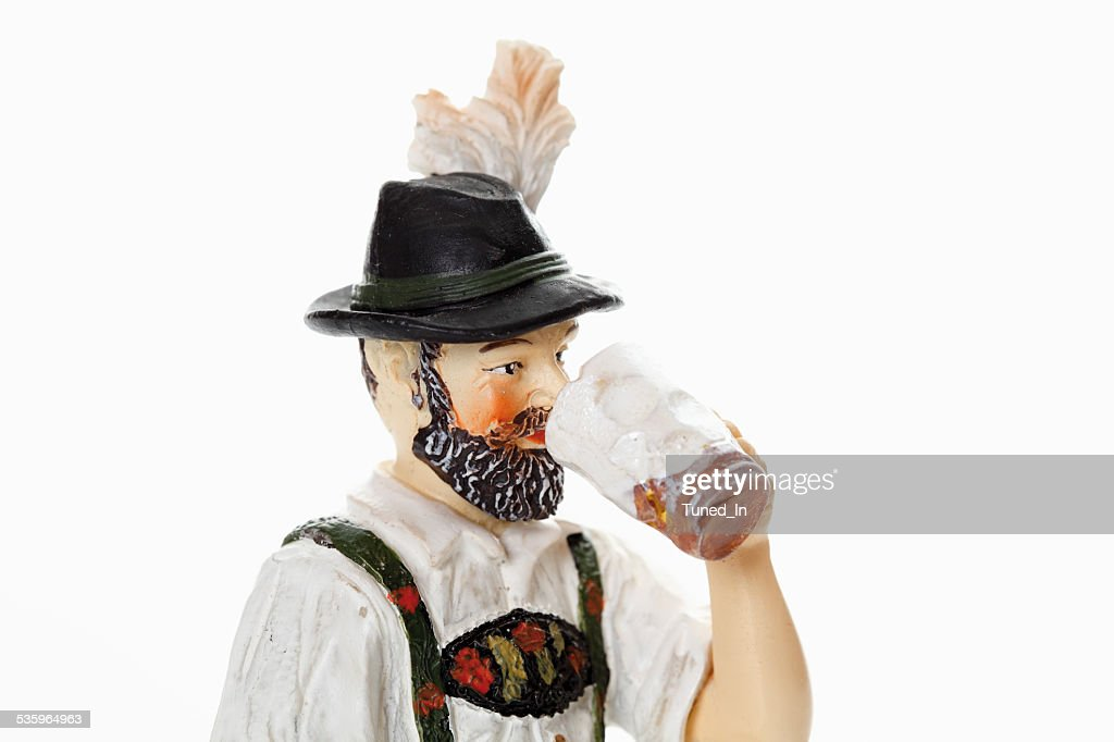 Bavarian figurine drinking beer from beer stein : Stock Photo