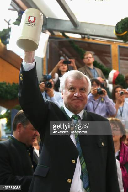 Bavarian Governor Horst Seehofer lifts up a beer mug at Schottenhamel beer tent on the opening day of the 2014 Oktoberfest at Theresienwiese on...