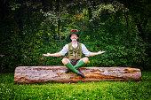 bavarian man sitting outdoors on tree stump and meditating