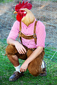 bavarian man with a chicken head kneeling outdoors