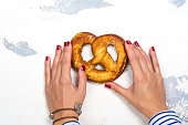 Woman's hands holding bavarian pretzel with salt