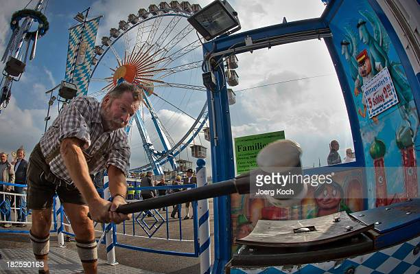 A bavarian visitor in a traditional 'Lederhosen' participates in a funfair attraction called 'Hau den Lukas' at the Oktoberfest 2013 beer festival at...