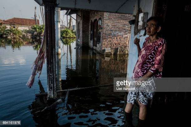 Bawon stands in front of her house submerged by rising sea levels on June 6 2017 in Pekalongan Indonesia Bawon with her family has been four years...