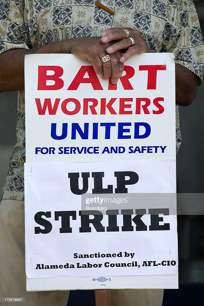 A Bay Area Rapid Transit (BART) employee with Service Employees International Union (SEIU) Local 1021 hold signs while picketing in front of the Lake Merritt BART station in Oakland, California, U.S., on Tuesday, July 2, 2013. Trains linking downtown San Francisco to its airport and the East Bay area are likely to remain idle today, officials said, as a strike entered its second day, forcing about 400,000 riders to commute by car, bus or ferry. Photographer: David Paul Morris/Bloomberg via Getty Images