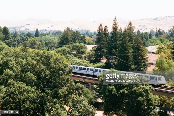 A Bay Area Rapid Transit train is seen passing through trees and the Diablo Foothills in downtown Walnut Creek California July 26 2017