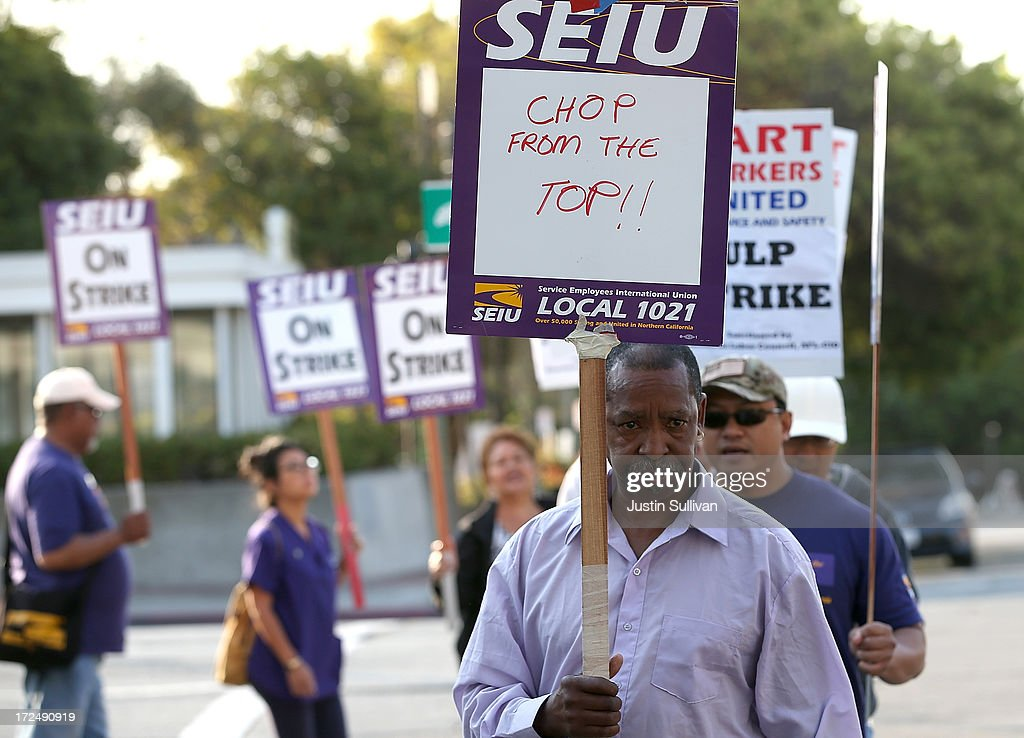 Bay Area Rapid Transit (BART) union workers with SEIU Local 1021 hold signs as they picket in front of the Lake Merritt station on July 2, 2013 in Oakland, California. For a second day, hundreds of thousands of San Francisco Bay Area commuters are scrambling to find ways to work after two of San Francisco Bay Area Rapid Transit's (BART) largest unions went on strike early yesterday morning following contract negotiations with management falling apart the day before. Train operators, mechanics, station agents and maintenance workers are seeking a five percent wage increase and are fighting management who want to have workers to begin contributing to their pensions, pay more for health insurance and reduce overtime expenses.