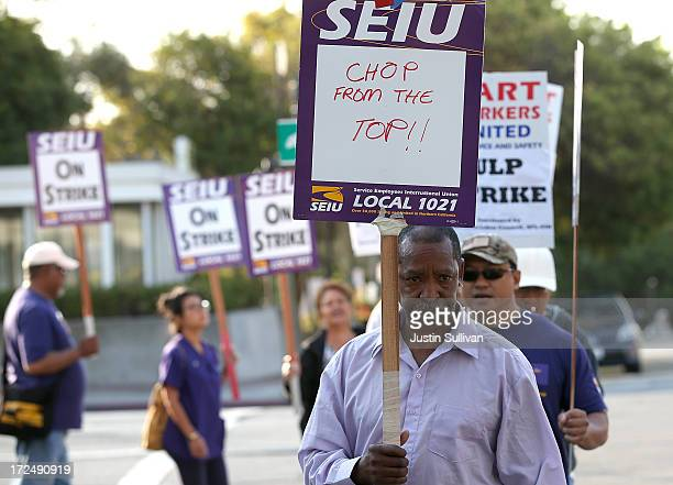 Bay Area Rapid Transit union workers with SEIU Local 1021 hold signs as they picket in front of the Lake Merritt station on July 2 2013 in Oakland...