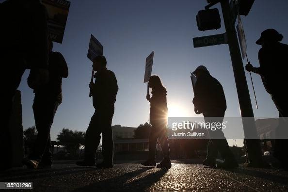 Bay Area Rapid Transit workers carry signs as they picket in front of the Lake Merritt BART station on the first day of the BART strike on October 18...