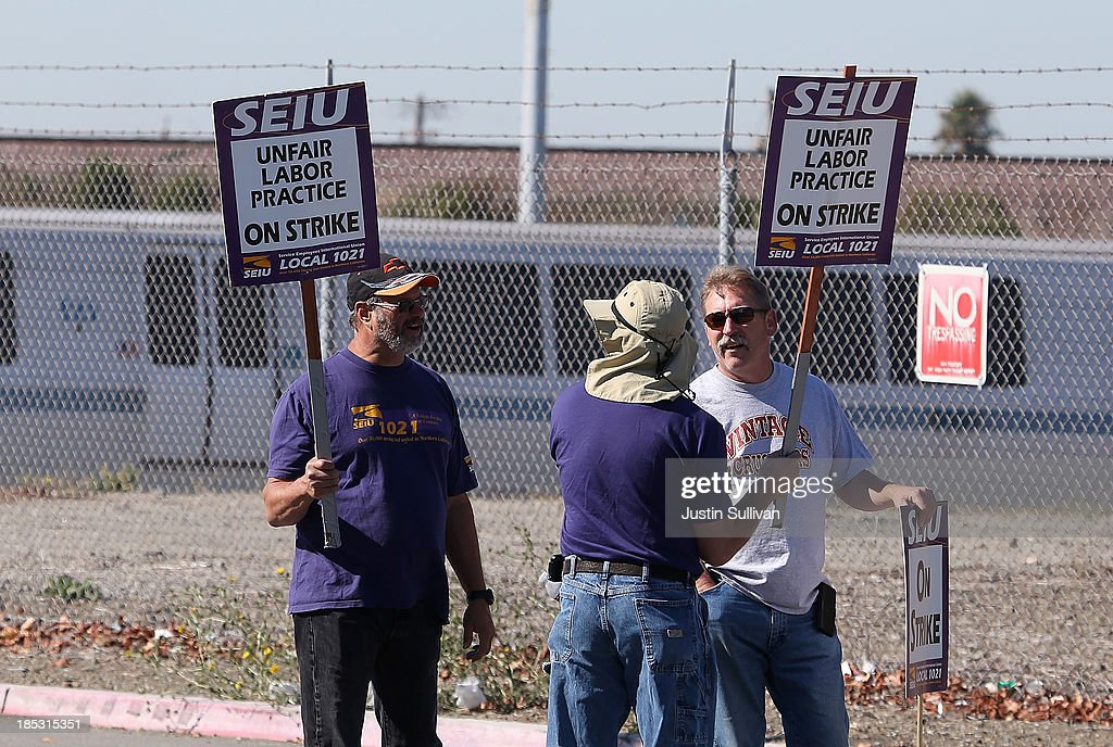 Bay Area Rapid Transit (BART) workers hold signs as they picket outside of a BART maintenance facility on the first day of the BART strike on October 18, 2013 in Richmond, California. For the second time this year, BART workers have gone on strike after contract negotiations between BART management and the transit agency's two largest unions fell apart yesterday afternoon. Management and unions agreed on the financial specifics of the contract but differed on workplace safety rules.
