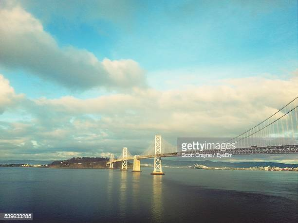 Bay Bridge Over River Against Cloudy Sky