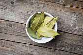 Bay leaves in white bowl. Close up