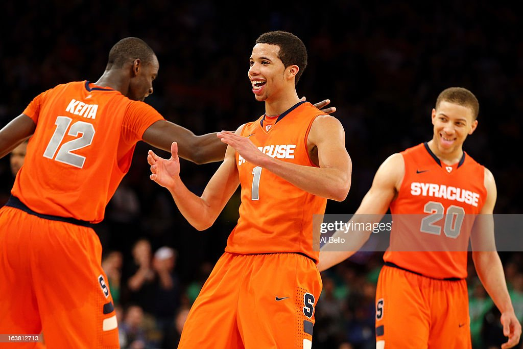 Baye Keita #12, Michael Carter-Williams #1 and Brandon Triche #20 of the Syracuse Orange celebrate in the final seconds of their 58-55 overtime win against the Georgetown Hoyas during the semifinals of the Big East Men's Basketball Tournament at Madison Square Garden on March 15, 2013 in New York City.