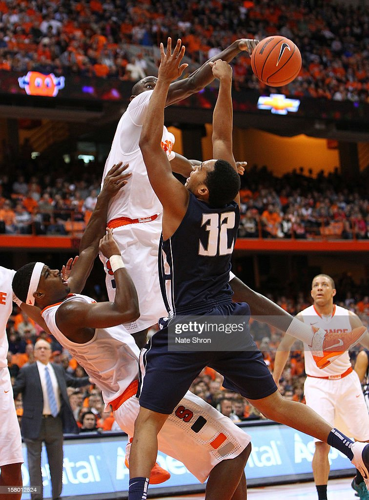 Baye Moussa Keita #12 of the Syracuse Orange blocks the shot as he falls backwards on top of <a gi-track='captionPersonalityLinkClicked' href=/galleries/search?phrase=C.J.+Fair&family=editorial&specificpeople=7366451 ng-click='$event.stopPropagation()'>C.J. Fair</a> #5 against Ed Waite #32 of the Monmouth Hawks during the game at the Carrier Dome on December 8, 2012 in Syracuse, New York.