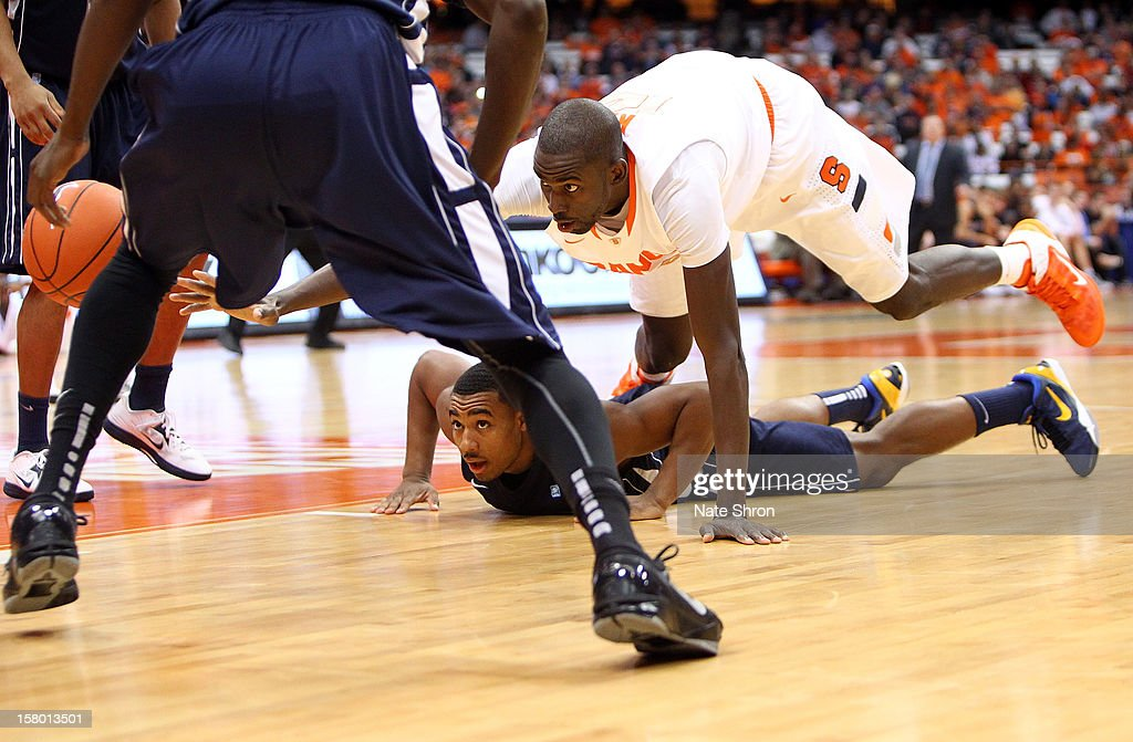 Baye Moussa Keita #12 of the Syracuse Orange dives for possession of the ball against Dion Nesmith #1 of the Monmouth Hawks during the game at the Carrier Dome on December 8, 2012 in Syracuse, New York.