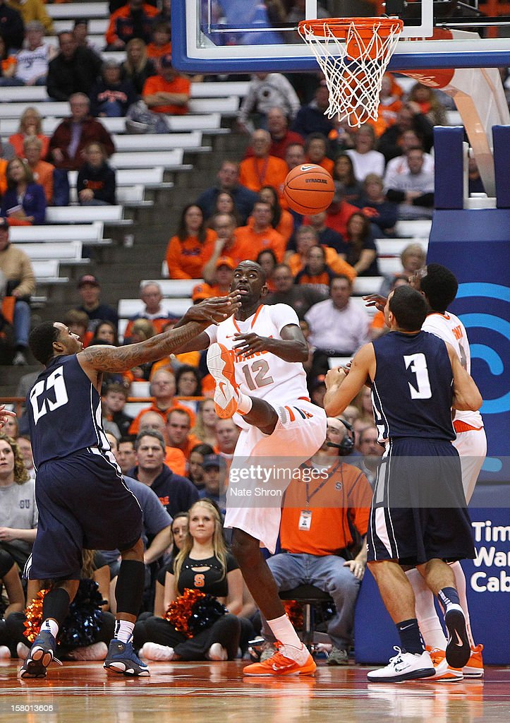 Baye Moussa Keita #12 of the Syracuse Orange falls backwards as he reaches for the rebound with teamate Jerami Grant #3 against Gary Cox #25 and Max DiLeo #3 of the Monmouth Hawks during the game at the Carrier Dome on December 8, 2012 in Syracuse, New York.