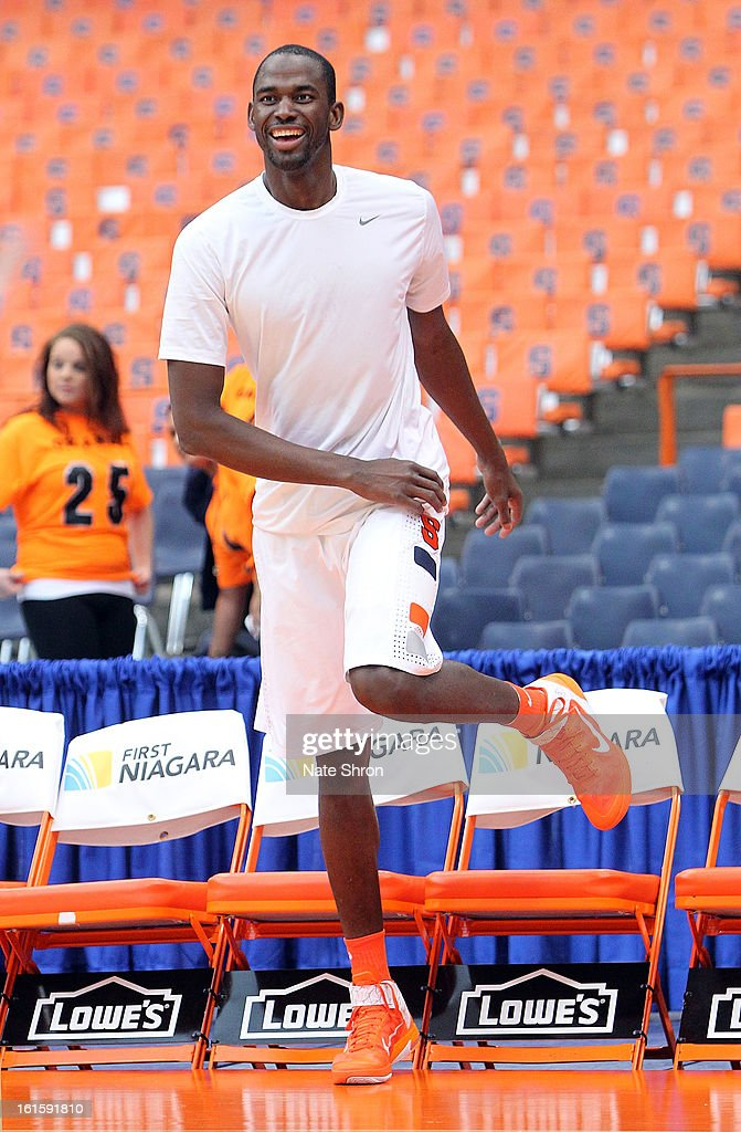 Baye Moussa Keita #12 of the Syracuse Orange smiles as he steps over the bench during warm ups prior to the game against the St. John's Red Storm at the Carrier Dome on February 10, 2013 in Syracuse, New York.