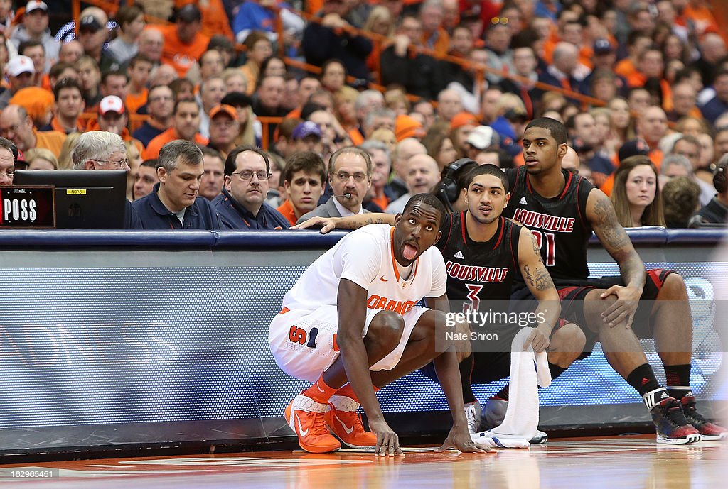 Baye Moussa-Keita #12 of the Syracuse Orange kneels on the sideline as he waits to check in to the game with <a gi-track='captionPersonalityLinkClicked' href=/galleries/search?phrase=Peyton+Siva&family=editorial&specificpeople=5792001 ng-click='$event.stopPropagation()'>Peyton Siva</a> #3 and Chane Behanan #21 of the Louisville Cardinals during the game at the Carrier Dome on March 2, 2013 in Syracuse, New York.