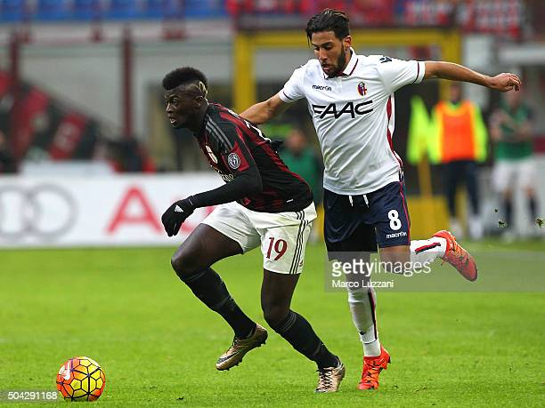 Baye Niang of AC Milan competes for the ball with Saphir Sliti Taider of Bologna FC during the Serie A match between AC Milan and Bologna FC at...