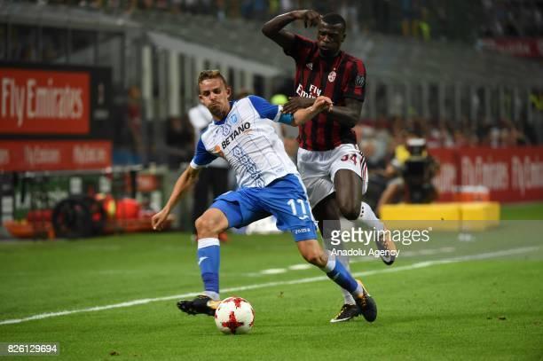 Baye Niang of AC Milan in action against Nicusor Bancu of CS U Craiova during UEFA Europa League Qualifying Round match between AC Milan and CS U...