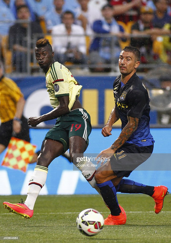 <a gi-track='captionPersonalityLinkClicked' href=/galleries/search?phrase=M%27Baye+Niang&family=editorial&specificpeople=7755200 ng-click='$event.stopPropagation()'>M'Baye Niang</a> #19 of AC Milan shoots the ball against <a gi-track='captionPersonalityLinkClicked' href=/galleries/search?phrase=Aleksandar+Kolarov&family=editorial&specificpeople=4329824 ng-click='$event.stopPropagation()'>Aleksandar Kolarov</a> #11 of Manchester City during International Champions Cup 2014 at Heinz Field on July 27, 2014 in Pittsburgh, Pennsylvania.