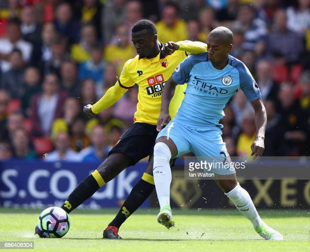 Baye Niang of Watford and Fernandinho of Manchester City battle for possession during the Premier League match between Watford and Manchester City at...