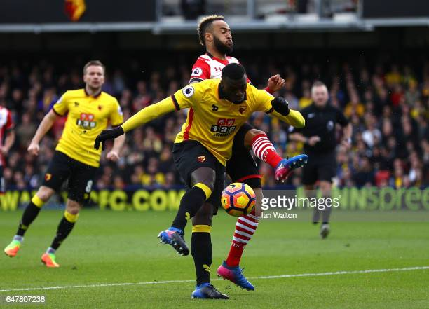 Baye Niang of Watford volleys the ball towards goal while Nathan Redmond of Southampton attempts to block during the Premier League match between...