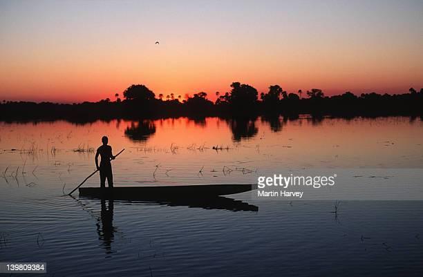 Bayei mokoro poler at sunset in the Okovango Delta. Okovango, Botswana.