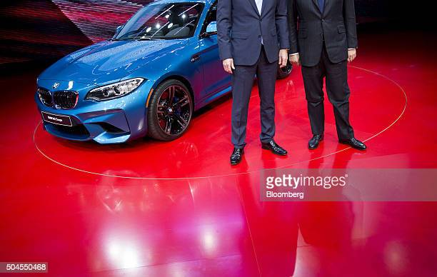 Bayerische Motoren Werke AG executives stand with the 2016 M2 highperformance coupe vehicle at the 2016 North American International Auto Show in...