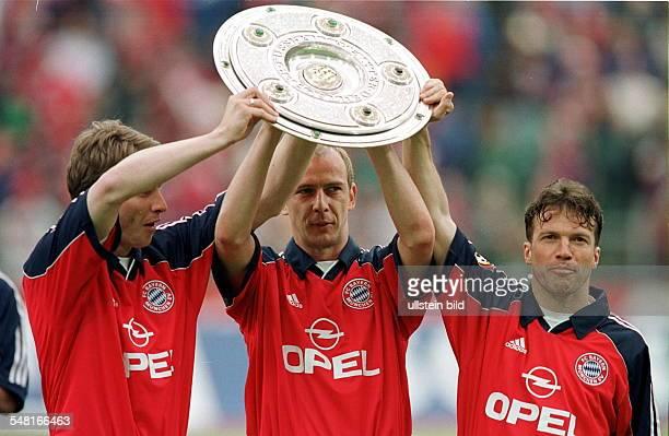 Bayern München Deutscher Meister 1998/99 die Münchner Spieler Michael Tarnat Mario Basler und Lothar Matthäus nach der Siegerehrung im Münchner...